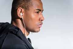 profile portrait of young african american man listening music in earphones and looking away stock images