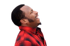 Profile portrait of young black man laughing and looking up. Against isolated white background royalty free stock image