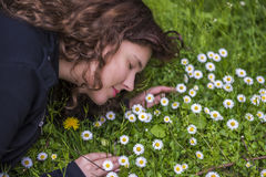 Profile portrait of young girl lying in a bed of white daisy wildflowers Royalty Free Stock Images
