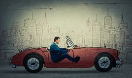Imaginary car driving. Profile portrait of a young smiling businessman driving a drawn race car in an imaginary city isolated on grey wall background stock image