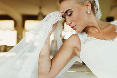 A profile of pretty blond bride holding her forehead while sitting thoughtful royalty free stock images
