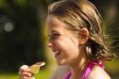 Profile of pretty girl outdoors. Outdoor profile of girl eating crisps Royalty Free Stock Photos