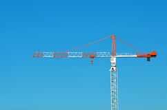 Profile of a red and white Tower crane against blue sky Stock Photo