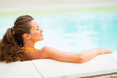 Profile relaxed young woman laying in pool Stock Photography