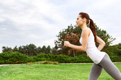 Profile of running woman in park. During process. Portrait of young slender woman in profile running against park background Stock Image