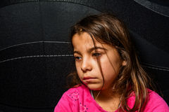 Profile of a Sad little girl is sitting in the corner of the room Stock Image
