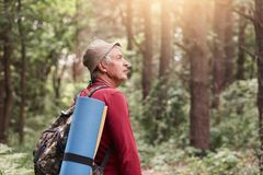 Profile of senior man looking aside attentively, going camping, wandering in forest, uniting with nature, having backpack and. Sleeping pad at his back stock photos