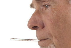 Profile of senior man with thermometer in his mout. Senior man taking temperature. Isolated on white Stock Image