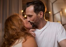 Voluptuous man and woman enjoying candid kiss. Profile of sensual senior loving couple kissing with passion. Their eyes are closed with pleasure Stock Photography