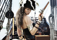 Profile of a Sexy Pirate female captain standing on the deck of her ship with pistol in hand. Royalty Free Stock Image