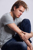 Profile of young man. With blonde hair and blue eyes, dressed in grey T-shirt and blue jeans, sitting on the stool and looking away stock photos