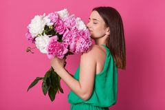 Profile shot of beautiful brunette girl holding with white and rose peonies, attractive woman with big bouquet, female smells. Flowers, dressed green sundress stock photography
