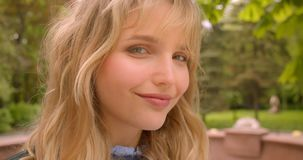 Profile shot of beautiful caucasian blonde student watching prettily into camera in the green city park. Profile shot of beautiful caucasian blonde student stock video footage