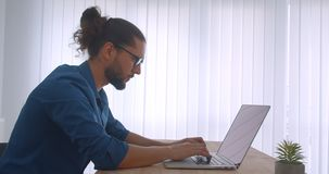 Profile shot of businessman with ponytail and eyeglasses working with laptop being busy and motivated in light office. Profile shot of businessman with ponytail stock video footage