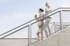 Profile shot of businesswomen moving down stairs against sky Royalty Free Stock Photography