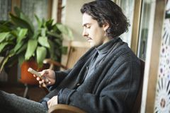 Spanish young man using smartphone sitting on a terrace. Profile shot portrait of a white young man with blue eyes, moustache, long hair and ear ring using a Stock Images
