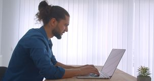 Profile shot of progressive businessman with ponytail working with laptop being busy and concentrated in light office. Profile shot of progressive businessman stock video footage