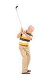 Profile shot of a senior swinging a golf club Royalty Free Stock Image