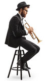Profile shot of a trumpet player seated on a chair. Isolated on white background Stock Images