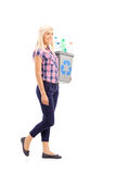 Profile shot of a woman carrying a recycle bin Royalty Free Stock Photography