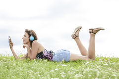 Profile shot of woman listening to music through cell phone using headphones while lying on grass against sky Royalty Free Stock Photo