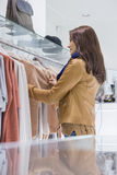 Profile shot of woman selecting sweater in store Royalty Free Stock Images