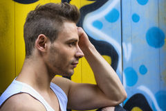 Profile shot of young man next to bright colored graffiti Stock Images