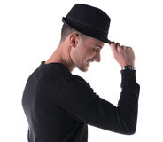 Profile shot of young man smiling, touching fedora hat. On his head, isolated on white royalty free stock photography