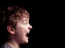 Profile of the shouting boy. On a black background Royalty Free Stock Photography