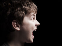 Profile of the shouting boy. On a black background Stock Photo