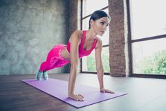 Profile side view of her she nice beautiful adorable attractive charming lady wearing pink outfit look standing in plank. Leaning on hands fitness in modern stock photography
