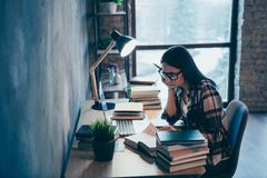 Profile side view of nice attractive smart clever intelligent brunette lady in checked shirt researching marketing. Materials pile stack at industrial loft stock images