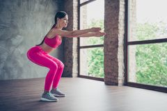 Profile side view of nice beautiful graceful attractive thin lady doing situps in modern loft industrial interior style royalty free stock image
