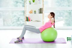 Profile side view photo of concentrated focused aimed purposeful. Energetic woman using green fit ball for doing crunches wearing tight leggings casual pink Royalty Free Stock Photography