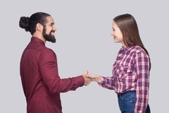 Profile side view portrait of happy bearded man and woman in casual style standing and shaking their hands with toothy smile. stock photos