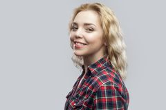 Profile side view portrait of happy beautiful blonde young woman in casual red checkered shirt standing and looking at camera with royalty free stock photography