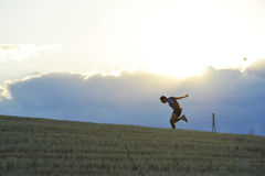 Profile silhouette of young man running in countryside practicing final sprint on sunset Royalty Free Stock Images