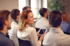 Profile of smiling woman in audience on lecture on company meeti Royalty Free Stock Images
