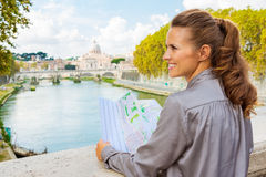 Profile of smiling woman holding map in Rome on Tiber River Royalty Free Stock Images