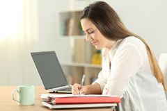 Profile of a student taking notes at home. Profile of a student taking notes on a notebook at home stock photo
