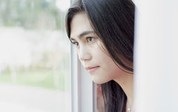 Profile of teen girl looking out window Stock Image