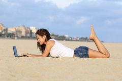 Profile of a teenager girl browsing her laptop lying on the sand of the beach. With a city in the background Royalty Free Stock Photography