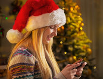 Profile teenager girl in santa hat writing sms Royalty Free Stock Photo