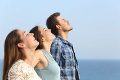 Profile of three friends breathing fresh air on the beach royalty free stock images