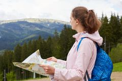 Profile of traveler woman visiting high mountins, pretty dark haired girl with map in hands and blue backpack searching right way. Enjoying view of mountainous stock image