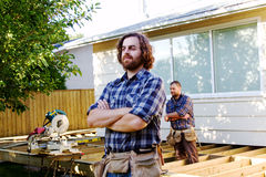 Profile of two carpenters. Two carpenters standing with arms crossed royalty free stock photography