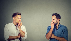 Profile of two preoccupied businessmen looking at each other. Side profile of two preoccupied businessmen looking at each other royalty free stock image