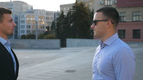 Profile of two young business men standing outdoor and talking. Businessmen meet and speaking outside in the city with. Blue sky at background. Communication of stock footage