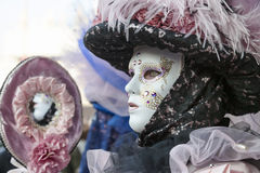Profile of a Venetian Mask. Venice, Italy-February 18,2012: Portrait of a woman wearing a traditional disguise with a mirror in Venice during The Carnival days Royalty Free Stock Images