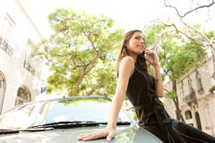 Businesswoman leaning on car with phone. Stock Photos